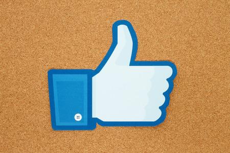 social networking service: KIEV, Ucrania - 10 de enero 2015: los pulgares de Facebook encima de la muestra impresa en papel y se coloca en el tabl�n de corcho. Facebook es una red social muy conocida.