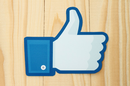 thumbs up sign: KIEV, UKRAINE - JANUARY 10, 2015: Facebook thumbs up sign printed on paper and placed on wooden background. Facebook is a well-known social networking service. Editorial