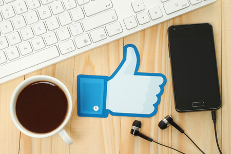 KIEV, UKRAINE - JANUARY 10, 2015: Facebook thumbs up sign printed on paper and placed on wooden background with coffee, keyboard and smart phone. Facebook is a well-known social networking service. Editorial