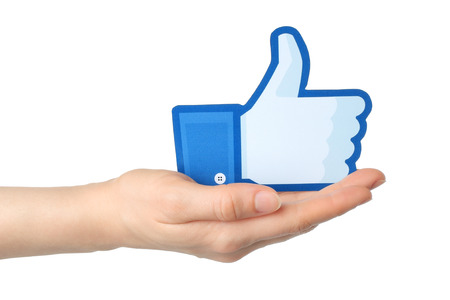KIEV, UKRAINE - JANUARY 24, 2015: Hand holds facebook thumbs up sign printed on paper on white background. Facebook is a well-known social networking service.