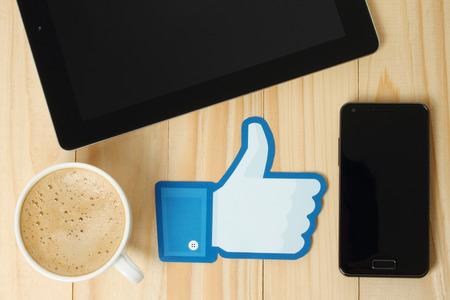 social networking service: KIEV, Ucrania - 24 de enero de 2015: los pulgares de Facebook encima de la muestra impresa en papel y se coloca en el fondo de madera con el caf�, el iPad y el tel�fono inteligente. Facebook es una red social muy conocida.