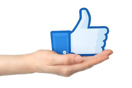 social networking service: KIEV, Ucrania - 24 de enero 2015: La mano sostiene facebook pulgar hacia arriba signo impreso en papel sobre fondo blanco. Facebook es una red social muy conocida.