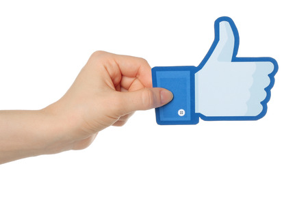social networking service: KIEV, UKRAINE - JANUARY 24, 2015: Hand holds facebook thumbs up sign printed on paper on white background. Facebook is a well-known social networking service.