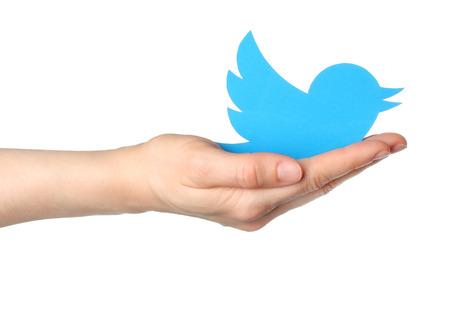 KIEV, UCRÂNIA - 16 de janeiro de 2015: A mão prende Twitter logotipo pássaro impresso em papel. Twitter é um serviço de rede social on-line que permite aos usuários enviar e ler mensagens curtas.
