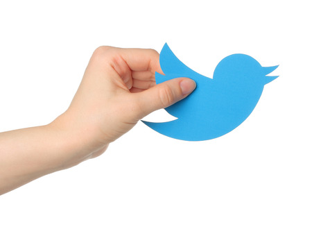 KIEV, UKRAINE - JANUARY 16, 2015: Hand holds twitter logotype bird printed on paper. Twitter is an online social networking service that enables users to send and read short messages. 新聞圖片