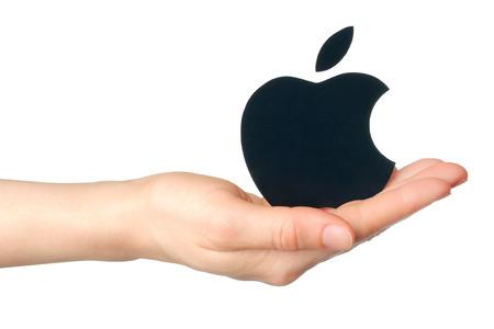 KIEV, UCRÂNIA - 16 de fevereiro de 2015: A mão prende logotipo da maçã impresso em papel em background.Apple branco é uma empresa multinacional americana, que vende produtos eletrônicos de consumo e computadores pessoais. Editorial