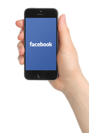 KIEV, UKRAINE - MARCH 7, 2015:Hand holds iPhone 5s Space Gray with Facebook logo on white background. Facebook is a well-known social networking service.