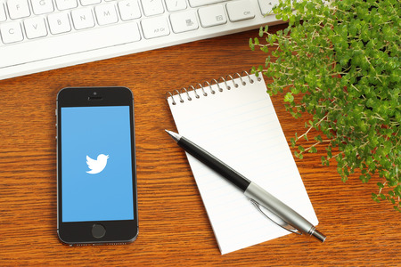 KIEV, UKRAINE - MARCH 7, 2015:iPhone with Twitter logotype on its screen and keyboard, notepad, pen, green plant on wooden background Stock Photo - 37759343