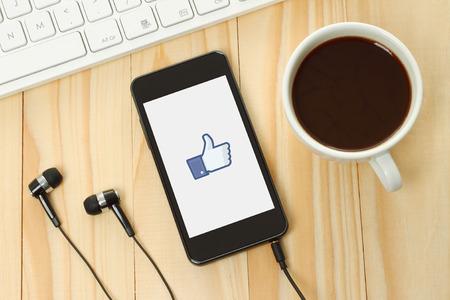 KIEV, UCRÂNIA - 10 de janeiro de 2015: Telefone esperto com Facebook polegares acima do sinal em sua tela e fones de ouvido, teclado, copo de café no fundo de madeira.