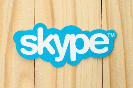 background skype: KIEV, UKRAINE - FEBRUARY 19, 2015: Skype logotype printed on paper and placed on wood background. Skype is a telecommunications application software developed by Microsoft. Editorial