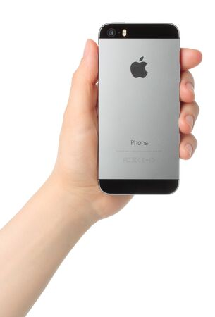 KIEV, UKRAINE - MARCH 7, 2015:Hand holds iPhone 5s Space Gray on white background.iPhone is a line of smartphones designed by Apple Inc.
