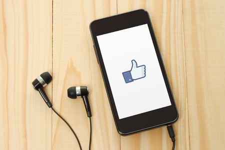 KIEV, UKRAINE - JANUARY 10, 2015: Smart phone with Facebook thumbs up sign on its screen and headphones on wooden background.