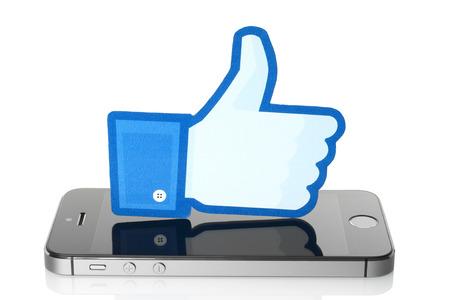 social networking service: KIEV, Ucrania - 07 de marzo 2015: los pulgares de Facebook encima de la muestra impresa en papel y se coloca en el iPhone en el fondo blanco. Facebook es una red social muy conocida.