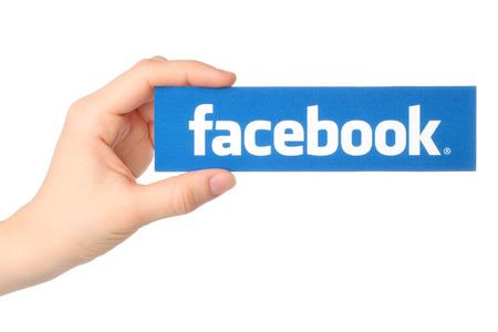 KIEV, UCRÂNIA - 07 de março de 2015: A mão prende logo facebook impresso em papel no fundo branco. Facebook é um serviço de rede social bem conhecido.