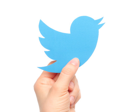 KIEV, UKRAINE - MARCH 7, 2015: Hand holds twitter logotype bird printed on paper. Twitter is an online social networking service that enables users to send and read short messages. Imagens - 37759429