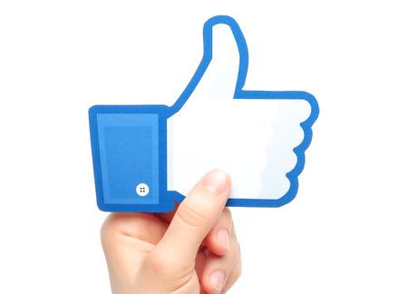 social networking service: KIEV, Ucrania - 07 de marzo 2015: La mano sostiene facebook pulgar hacia arriba signo impreso en papel sobre fondo blanco. Facebook es una red social muy conocida.