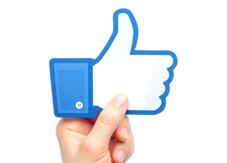 famous industries: KIEV, UKRAINE - MARCH 7, 2015: Hand holds facebook thumbs up sign printed on paper on white background. Facebook is a well-known social networking service.