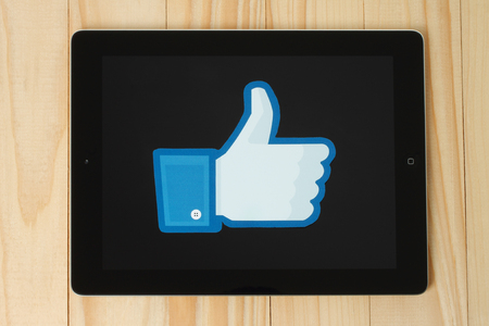 KIEV, UKRAINE - JANUARY 24, 2015: Facebook thumbs up sign printed on paper and placed on iPad on wooden background. Facebook is a well-known social networking service.