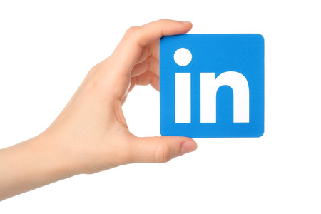KIEV, UKRAINE - MARCH 7, 2015:Hand holds Linkedin logo sign printed on paper on white background. Linkedin is a business social networking service. Imagens - 39070231