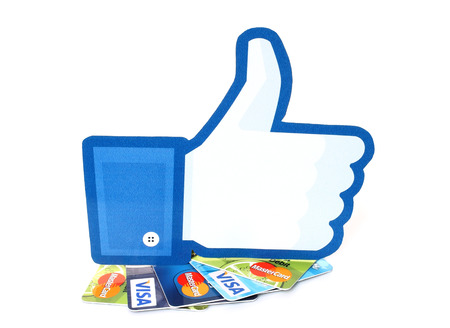 facebook: KIEV, UKRAINE - MARCH 21, 2015: Facebook thumbs up sign printed on paper and placed on cards Visa and MasterCard on white background.New Facebook payment concept. Editorial