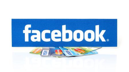 KIEV, UCRÂNIA - 21 de março de 2015: Facebook logo impresso em papel e colocados em cartões Visa e MasterCard no conceito branco pagamento background.New Facebook.