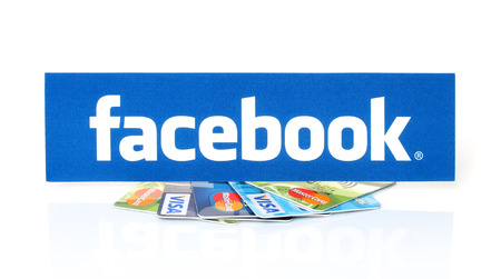 mastercard: KIEV, UKRAINE - MARCH 21, 2015: Facebook logo printed on paper and placed on cards Visa and MasterCard on white background.New Facebook payment concept. Editorial