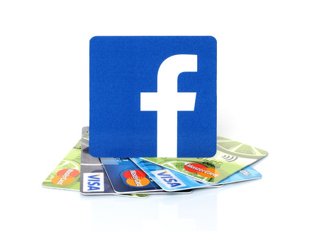 KIEV, UKRAINE - MARCH 21, 2015: Facebook logo printed on paper and placed on cards Visa and MasterCard on white background.New Facebook payment concept.