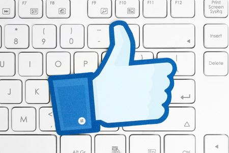 KIEV, UKRAINE - APRIL 15, 2015: Facebook thumbs up sign printed on paper and placed on white keyboard. Facebook is a well-known social networking service. Imagens - 39070375
