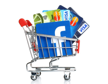 KIEV, UKRAINE - MARCH 21, 2015: Facebook logo printed on paper and placed into shopping cart with cards Visa and MasterCard on white background.New Facebook payment concept.
