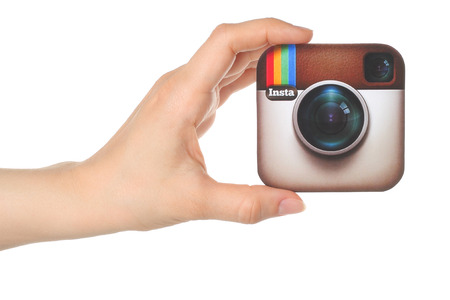 KIEV, UKRAINE - APRIL 30, 2015: Hand holds Instagram logo printed on paper on white background. Instagram is an online mobile photo-sharing, video-sharing service.