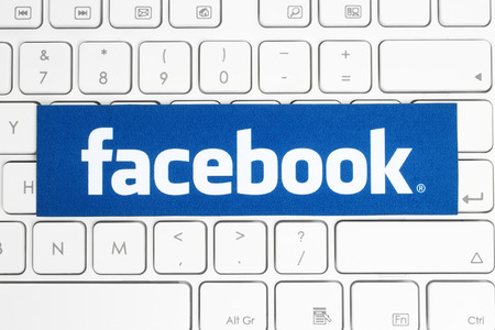 social networking service: KIEV, UKRAINE - APRIL 15, 2015: Facebook logo printed on paper and placed on white keyboard. Facebook is a well-known social networking service.