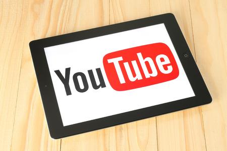 KIEV, UCRÂNIA - 30 de abril de 2015: logotipo do YouTube na tela do iPad no fundo de madeira. YouTube é um site de compartilhamento de vídeos