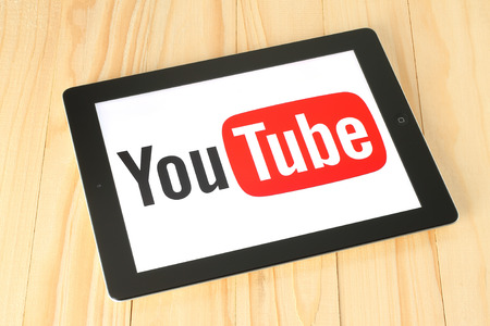 KIEV, UKRAINE - APRIL 30, 2015: YouTube logotype on iPad screen on wooden background. YouTube is a video-sharing website