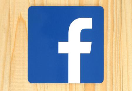 KIEV, UCRÂNIA - 30 de abril de 2015: Facebook logo sinal impresso em papel e colocou no fundo de madeira. Facebook é um serviço de rede social bem conhecido
