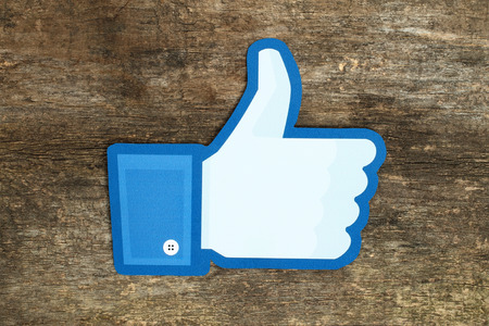 KIEV, UKRAINE - APRIL 15, 2015: Facebook thumbs up sign printed on paper and placed on wooden background. Facebook is a well-known social networking service Imagens - 42130775