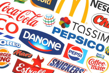 KIEV, UKRAINE - MAY 07, 2015:Collection of popular food logos companies printed on paper:Coca-Cola, Mars, Pepsico, Nestle, Tesco and others