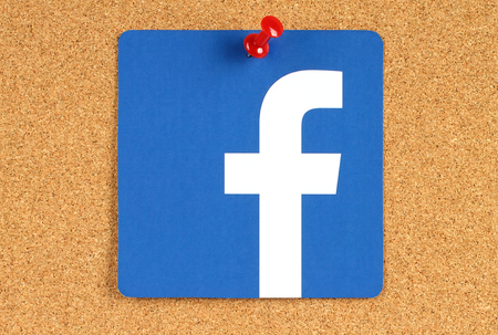 social networking service: KIEV, UKRAINE - MAY 25, 2015: Facebook logo sign printed on paper and  pinned on cork bulletin board. Facebook is a well-known social networking service