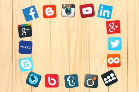 interaccion social: KIEV, Ucrania - julio 01, 2015: famosos iconos de redes sociales como: Facebook, Twitter, Blogger, Linkedin, Tumblr, Myspace y otros, impresos en papel y colocados alrededor en el fondo de madera.