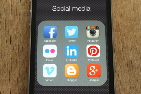 social media icons: KIEV, UKRAINE - JUNE 23, 2015: iPhone with popular social media icons on its screen on wooden background Editorial