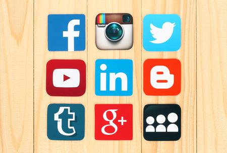 iconos: KIEV, Ucrania - 01 de julio 2015: famosos iconos de redes sociales como: Facebook, Twitter, Blogger, Linkedin, Tumblr, Myspace y otros, impresos en papel y se coloca en el fondo de madera. Editorial