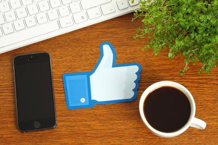 trabajo social: KIEV, Ucrania - 07 de marzo 2015: los pulgares de Facebook para arriba signo impreso en papel y se coloca en el fondo de madera con el café, el teclado y el teléfono inteligente. Facebook es una red social muy conocida. Editorial