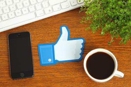 KIEV, UKRAINE - MARCH 07, 2015: Facebook thumbs up sign printed on paper and placed on wooden background with coffee, keyboard and smart phone. Facebook is a well-known social networking service. Editorial