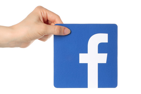 KIEV, UKRAINE - APRIL 30, 2015: Hand holds facebook logo printed on paper on white background. Facebook is a well-known social networking service. Imagens - 45701270
