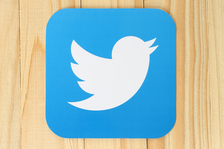 KIEV, UKRAINE - APRIL 30, 2015:Twitter logotype bird printed on paper. Twitter is an online social networking service that enables users to send and read short messages. Imagens - 45701272