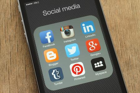 réseautage: Kiev, Ukraine - le 23 juin 2015: l'iPhone avec des icônes populaires de médias sociaux sur son écran sur fond de bois Éditoriale