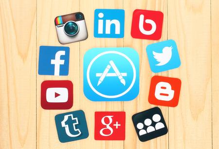 medios de informaci�n: KIEV, Ucrania - 01 de julio 2015: Alrededor AppStore icono se colocan iconos de redes sociales famosos, tales como: Facebook, Twitter, Blogger, Linkedin y otros, impreso en papel y se coloca en el fondo de madera.