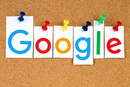 키예프, 우크라이나 - 2015 년 9 월 2 일 : 새로운 Google 로고가 종이에 인쇄되고 코르크 게시판에 자르고 고정됩니다 .Google은 인터넷 관련 서비스를 전문