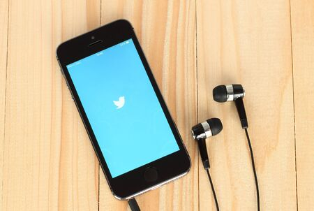 twitter: KIEV, UKRAINE - MAY 22, 2015:iPhone with Twitter logotype on its screen and headphones on wooden background