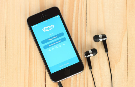 background skype: KIEV, UKRAINE - MAY 22, 2015:iPhone with Skype logotype on its screen and headphones on wooden background Editorial