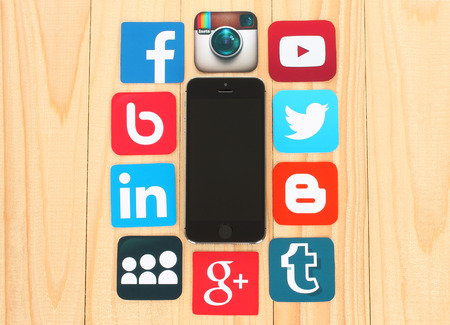 medios de comunicacion: KIEV, Ucrania - 01 de julio 2015: Facebook, Twitter, Blogger, Linkedin, Tumblr, Myspace y otros, impresos en papel y colocadas alrededor iPhone en fondo de madera: iconos tales como famosos medios de comunicación social